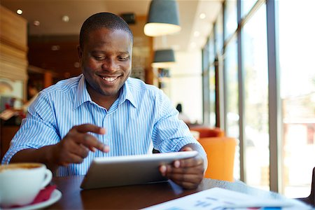 pressmaster (artist) - Image of happy young man using digital tablet in cafe Stock Photo - Budget Royalty-Free & Subscription, Code: 400-07668400