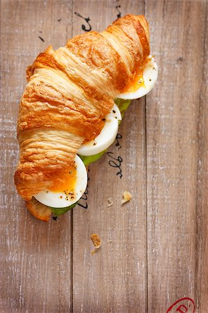 Fresh french croissant with boiled egg and salad for breakfast on a wooden board with copy space for text. Stock Photo - Budget Royalty-Free & Subscription, Code: 400-07675936