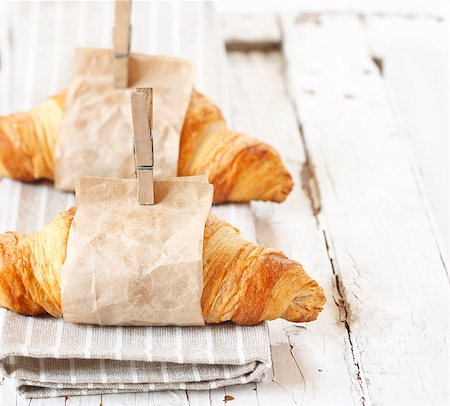 Fresh croissants wrapped in paper on an old white board. Stock Photo - Budget Royalty-Free & Subscription, Code: 400-07675937