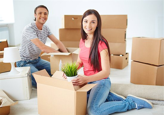 Happy young couple sitting on the floor of new flat and unpacking boxes Stock Photo - Royalty-Free, Artist: pressmaster, Image code: 400-07678148