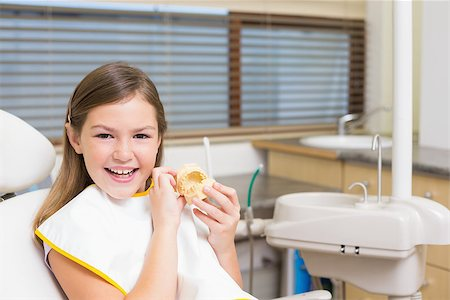 Little girl sitting in dentists chair holding model teeth at the dental clinic Stock Photo - Budget Royalty-Free & Subscription, Code: 400-07684919