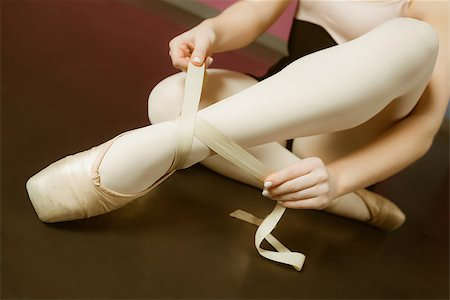 Ballerina tying the ribbon on her ballet slippers in the ballet studio Stock Photo - Budget Royalty-Free & Subscription, Code: 400-07725555