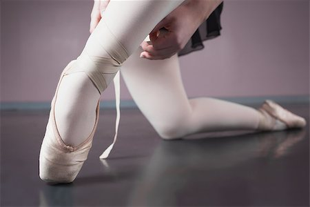 Ballerina tying the ribbon on her ballet slippers in the ballet studio Stock Photo - Budget Royalty-Free & Subscription, Code: 400-07725558