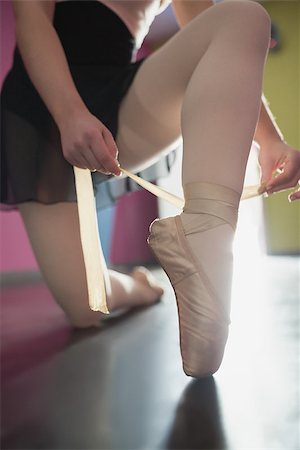 Ballerina tying the ribbon on her ballet slippers in the ballet studio Stock Photo - Budget Royalty-Free & Subscription, Code: 400-07725559