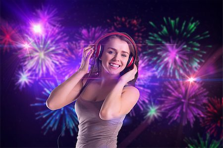 Pretty girl listening to music against digitally generated bright firework design Stock Photo - Budget Royalty-Free & Subscription, Code: 400-07720928