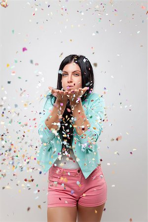 Young beautiful woman in party mood with confetti all around Stock Photo - Budget Royalty-Free & Subscription, Code: 400-07748142