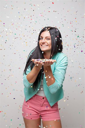 Young beautiful woman in party mood with confetti all around Stock Photo - Budget Royalty-Free & Subscription, Code: 400-07748143
