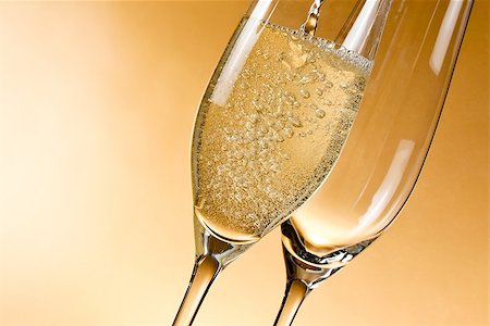 empty glasses of champagne and one being filled against golden background Stock Photo - Budget Royalty-Free & Subscription, Code: 400-07748191