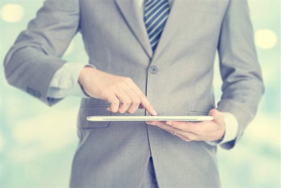 Close-up of male hands touching digital tablet, formal businessman standing with blur background. Stock Photo - Royalty-Free, Artist: szefei, Image code: 400-07748795