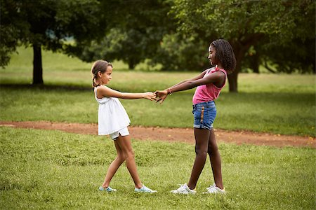 diego_cervo (artist) - Two hispanic and african little girls playing ring around the rosie in public park and holding hands Stock Photo - Budget Royalty-Free & Subscription, Code: 400-07774033