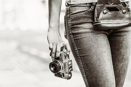Old fashioned picture of a girl holding a retro camera in the city Stock Photo - Budget Royalty-Free & Subscription, Code: 400-07778608