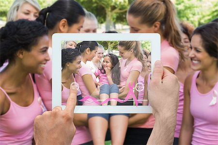Composite image of hand holding device showing photograph of breast cancer activists Stock Photo - Budget Royalty-Free & Subscription, Code: 400-07834698