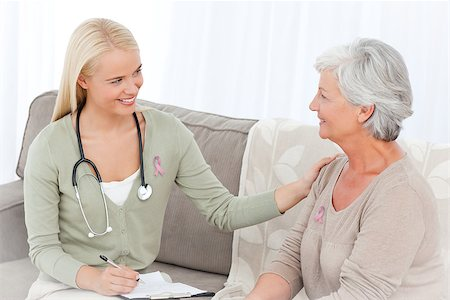 Doctor talking with her patient wearing breast cancer awareness ribbon Stock Photo - Budget Royalty-Free & Subscription, Code: 400-07835171