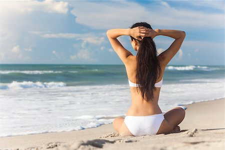 simsearch:400-04002563,k - A sexy young brunette woman or girl wearing a white bikini sitting on a deserted tropical beach with a blue sky Stock Photo - Budget Royalty-Free & Subscription, Code: 400-07894709