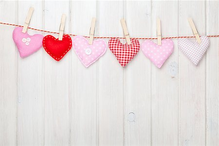 Valentines day toy hearts hanging on rope over white wooden background with copy space Stock Photo - Budget Royalty-Free & Subscription, Code: 400-07925323