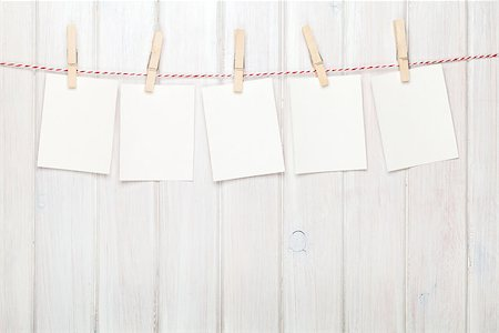 Photo frames hanging on rope over white wooden background Stock Photo - Budget Royalty-Free & Subscription, Code: 400-07922906