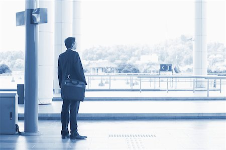 Rear view full body Asian Indian business man waiting bus at public bus station, in blue tone. Stock Photo - Budget Royalty-Free & Subscription, Code: 400-07978345