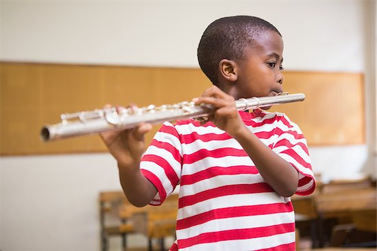 Cute pupil playing flute in classroom at the elementary school Stock Photo - Royalty-Free, Artist: 4774344sean, Image code: 400-07991063