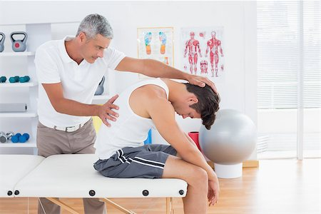 Doctor stretching a young man back in medical office Stock Photo - Budget Royalty-Free & Subscription, Code: 400-08018592