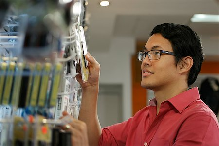 diego_cervo (artist) - Chinese sales clerk working in computer store, arranging and ordering cables and usb flash memory drives on shelf Stock Photo - Budget Royalty-Free & Subscription, Code: 400-08049953