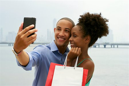diego_cervo (artist) - Black tourist heterosexual couple in Casco Antiguo Panama City with shopping bags. The man takes a selfie with his girlfiend and shopping bags with skyline in background Stock Photo - Budget Royalty-Free & Subscription, Code: 400-08054733