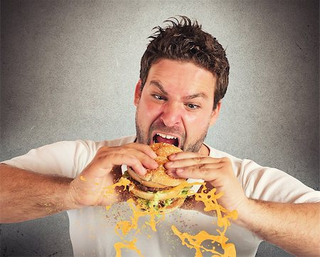Man eating a sandwich with violent impetuosity Stock Photo - Budget Royalty-Free & Subscription, Code: 400-08074207