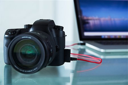 diego_cervo (artist) - Still life of dslr camera connected with USB cable to laptop computer on glass table. The photo camera is transferring images to PC in background. Copy space Stock Photo - Budget Royalty-Free & Subscription, Code: 400-08077777