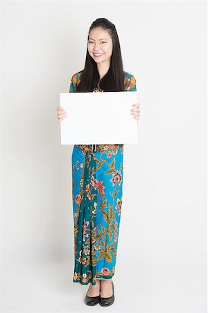 Full body portrait of Southeast Asian girl in batik dress hands holding white blank board, standing on plain background. Stock Photo - Budget Royalty-Free & Subscription, Code: 400-08113788