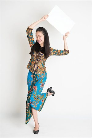 Full body portrait of Southeast Asian girl in batik dress hands holding white blank card jumping around on plain background. Stock Photo - Budget Royalty-Free & Subscription, Code: 400-08113789