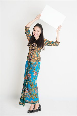 Full body portrait of Southeast Asian girl in batik dress hands holding white blank poster standing on plain background. Stock Photo - Budget Royalty-Free & Subscription, Code: 400-08113790