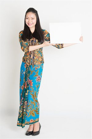 Full body portrait of Southeast Asian girl in batik dress hands holding white blank card, standing on plain background. Stock Photo - Budget Royalty-Free & Subscription, Code: 400-08113791