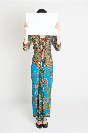 Full length Southeast Asian girl in batik dress holding a white card covering face standing on plain background. Stock Photo - Budget Royalty-Free & Subscription, Code: 400-08113792