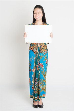 Full body portrait of Southeast Asian girl in batik dress hands holding white blank placard, standing on plain background. Stock Photo - Budget Royalty-Free & Subscription, Code: 400-08113793