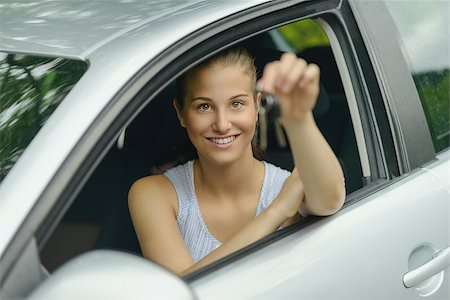 Young Pretty Woman Sitting Inside her Car, Smiling at the Camera While Showing Keys on her Hand. Stock Photo - Budget Royalty-Free & Subscription, Code: 400-08162226