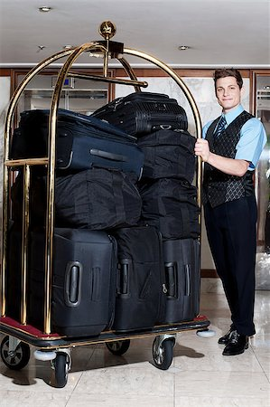 Handsome male concierge posing with a pile of bags in luggage cart Stock Photo - Budget Royalty-Free & Subscription, Code: 400-08185264