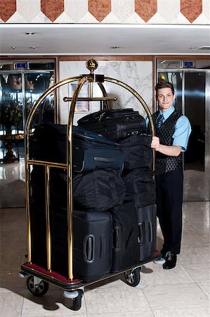 Bell boy pushing cart loaded with luggage to the guests room Stock Photo - Budget Royalty-Free & Subscription, Code: 400-08185263
