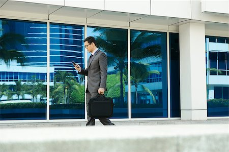 diego_cervo (artist) - Young chinese businessman commuting to office with computer bag and reading message on mobile phone. The man types while walks Stock Photo - Budget Royalty-Free & Subscription, Code: 400-08222925