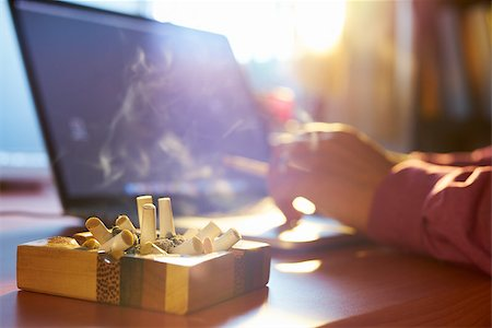 diego_cervo (artist) - Close up of ashtray full of cigarette, with man in background working on laptop computer and smoking indoors on early morning. Concept of addiction and abuse of nicotine. Stock Photo - Budget Royalty-Free & Subscription, Code: 400-08223129