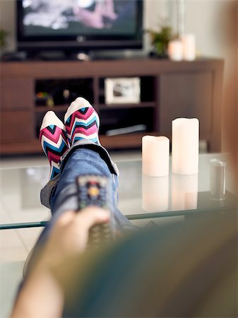 diego_cervo (artist) - Young caucasian woman laying on sofa with colourful socks. She puts her feet on table and relaxes. The girl watches TV and holds remote control. Focus on socks Stock Photo - Budget Royalty-Free & Subscription, Code: 400-08223202