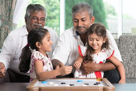 Happy multi generations Asian Indian family playing carom game at home. Grandparent, parent and children indoor lifestyle. Stock Photo - Budget Royalty-Free & Subscription, Code: 400-08223277