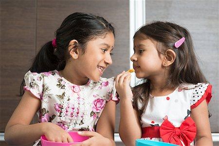 Eating traditional snack murukku. Cute Indian Asian girls enjoying food. Beautiful children model at home. Stock Photo - Budget Royalty-Free & Subscription, Code: 400-08223272