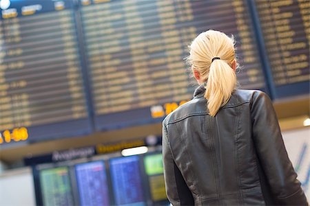Casually dressed young stylish female traveller checking a departures board at the airport terminal hall in front of check in couters. Flight schedule display blured in the background. Focus on woman. Stock Photo - Budget Royalty-Free & Subscription, Code: 400-08283878