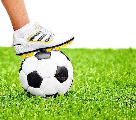 Football player, men foot on the ball, playing sport game at outdoor stadium, green grass field, isolated on white with text space, conceptual image of competition, goal and healthy active lifestyle Stock Photo - Budget Royalty-Free & Subscription, Code: 400-08299232