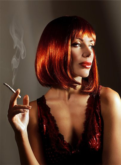 Beautiful woman smoke cigarette, pretty young lady with red hair isolated on dark background, attractive girl in red fashionable dress enjoying cigaret, cute smoker female with luxury hairstyle Stock Photo - Royalty-Free, Artist: Anna_Omelchenko, Image code: 400-08299262