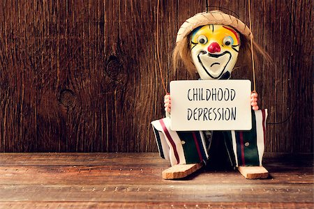 closeup of an old marionette with its face painted as a sad clown holding a signboard with the text childhood depression Stock Photo - Budget Royalty-Free & Subscription, Code: 400-08378246