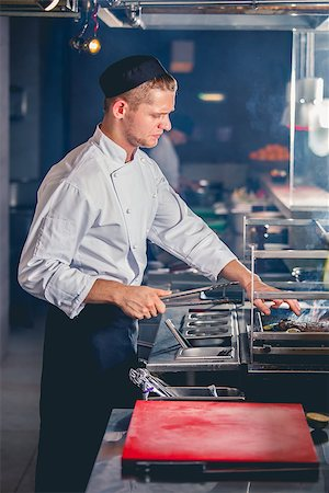 young male cook preparing meal on the grill with metal tongs in hand Stock Photo - Budget Royalty-Free & Subscription, Code: 400-08402074