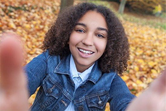 Beautiful happy mixed race African American girl teenager female child smiling with perfect teeth taking selfie photograph Stock Photo - Royalty-Free, Artist: darrenbaker, Image code: 400-08430069