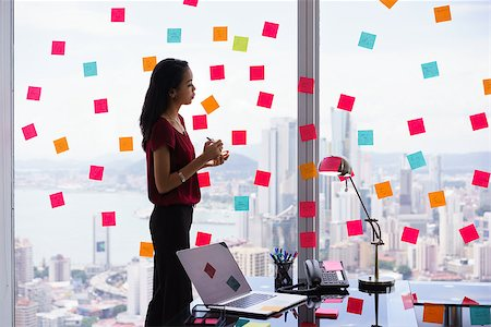 diego_cervo (artist) - Mixed race secretary working in modern office in skyscraper, writing and sticking adhesive notes with tasks on window. Stock Photo - Budget Royalty-Free & Subscription, Code: 400-08432851