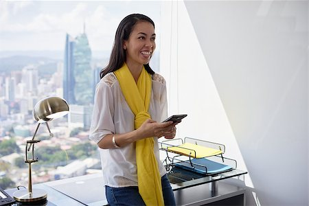 diego_cervo (artist) - Young multiethnic Chinese Hispanic woman leaning on table in a modern office building, with sight of the city. She holds a mobile phone and smiles happy Stock Photo - Budget Royalty-Free & Subscription, Code: 400-08432917
