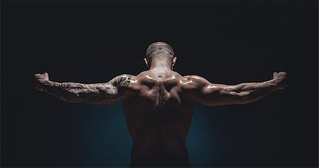 muscular male Bodybuilder posing in studio over black Stock Photo - Budget Royalty-Free & Subscription, Code: 400-08493242